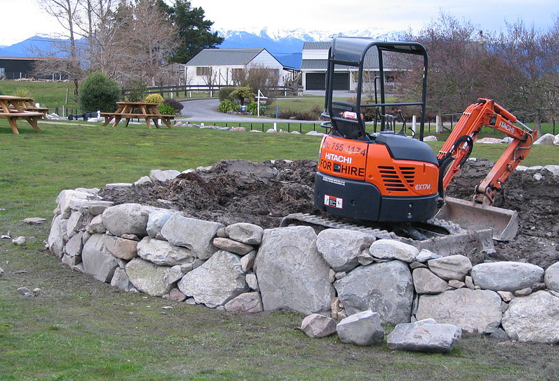 Machine and hand stacked rock wall to form a large raised planter bed at a commercial premises